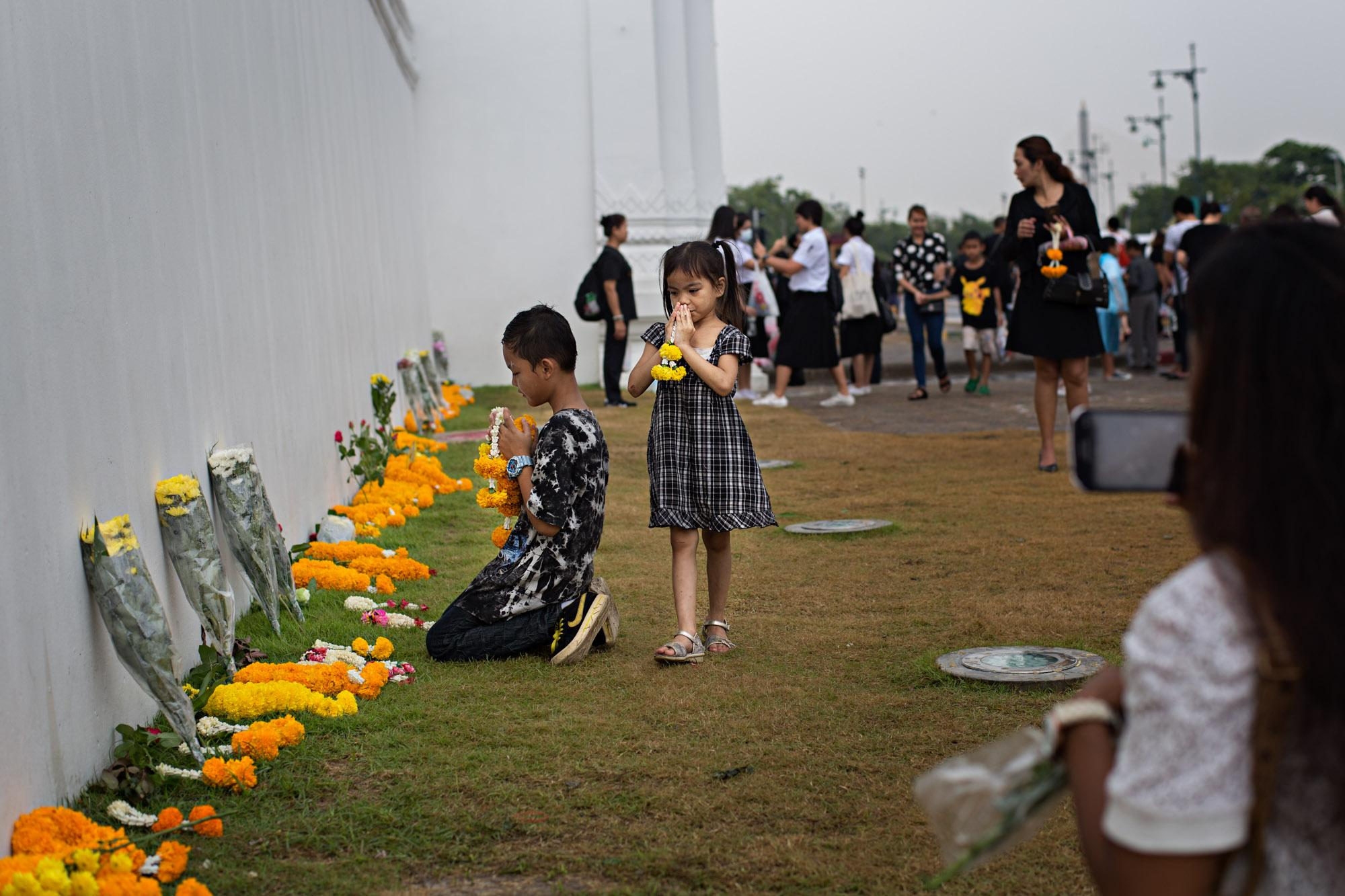 Children pay their respects to the late King Bhumibol Adulyadej at the Grand Palace in Bangkok, Thailand.