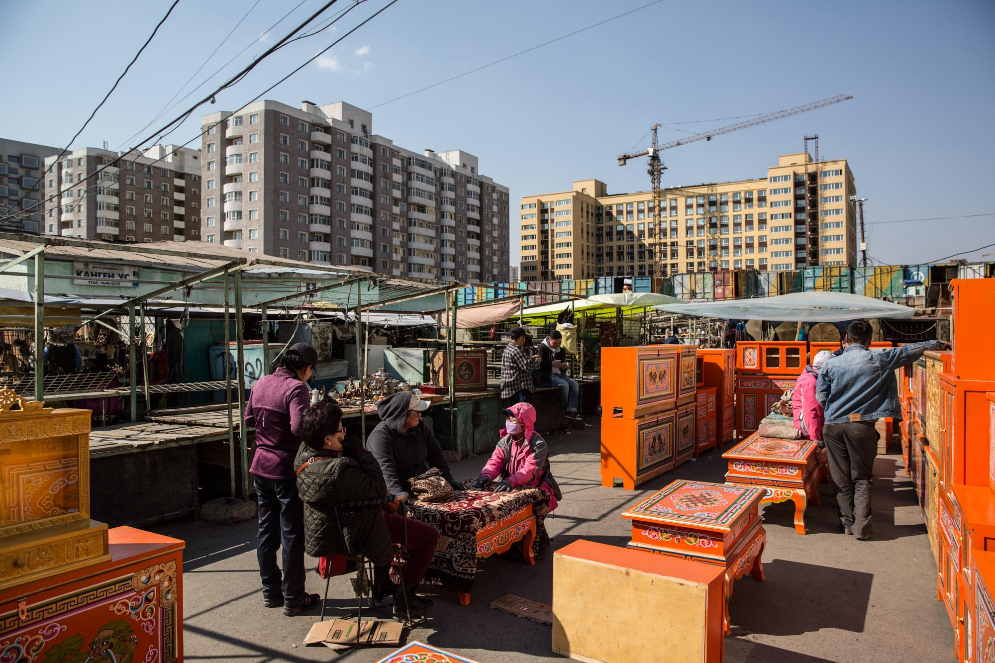 Vendors sit in a market in Ulaanbataar, Mongolia. Behind them, high rise apartments dominate the landscape.