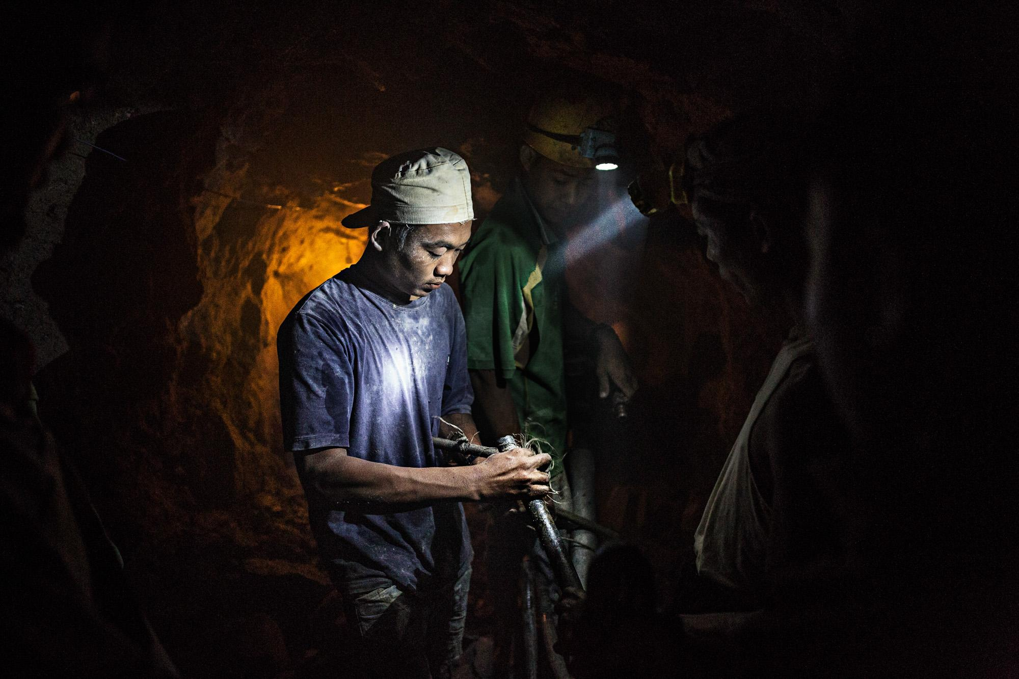 "Gold miners assemble a pneumatic drill in a privately owned mine several hours west of Mandalay, Myanmar. Many miners die from what the people call ""gun-disease,"" so named because the Burmese word for ""drill"" translates to ""gun."" It is caused by the dust from certain types of rocks and makes those infected susceptible to tuberculosis."