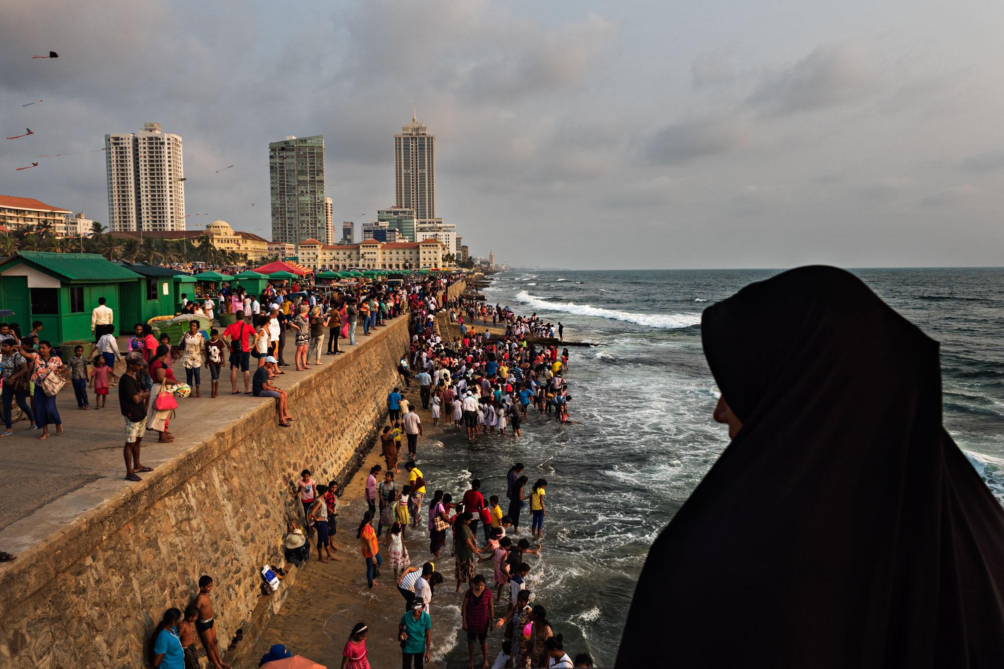 A woman looks out over people enjoying the beach at Galle Face Green in Colombo, Sri Lanka.