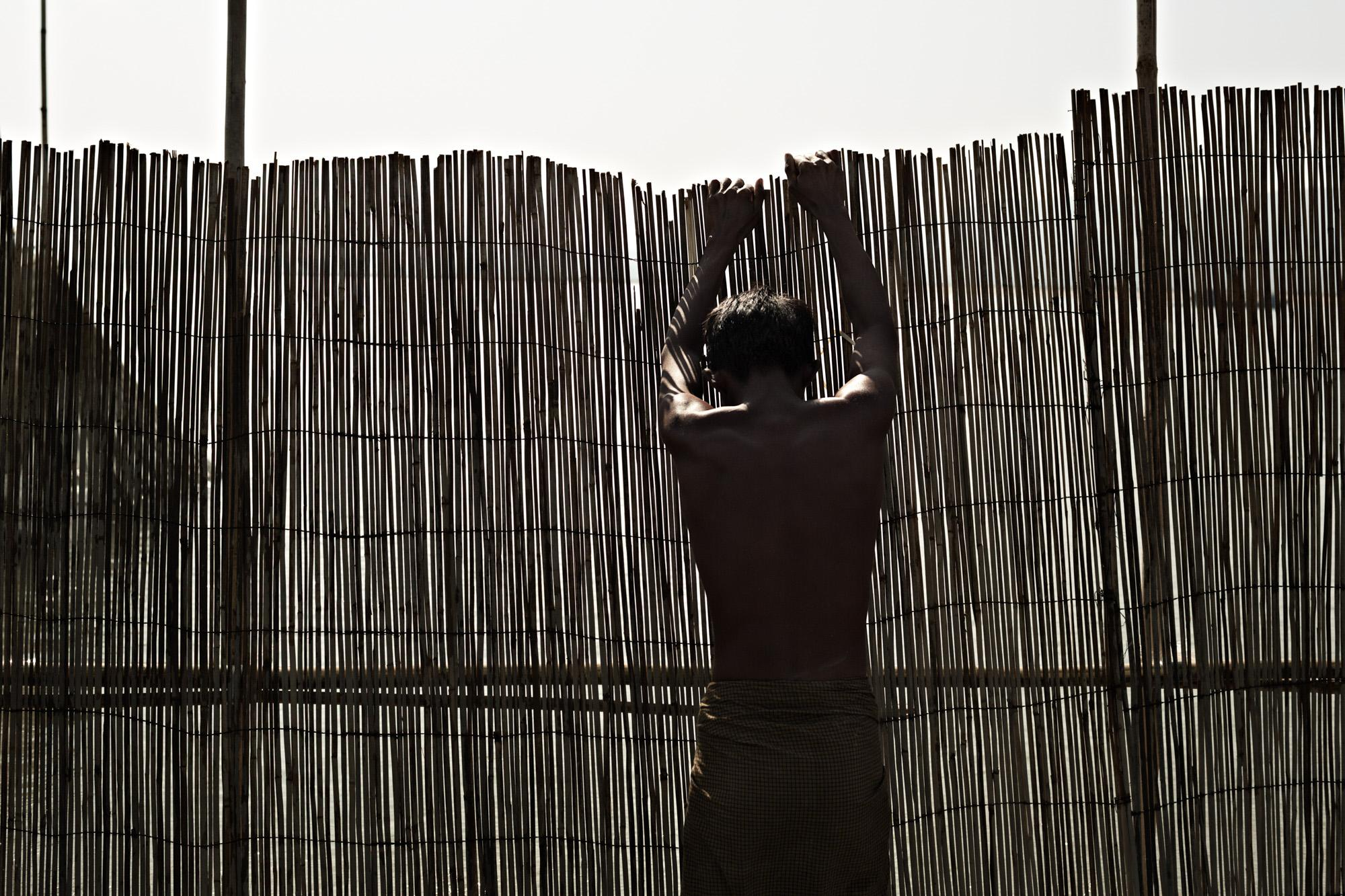 A fisherman puts up bamboo fencing to channel fish from the Irrawaddy River into a net near Mandalay, Myanmar.