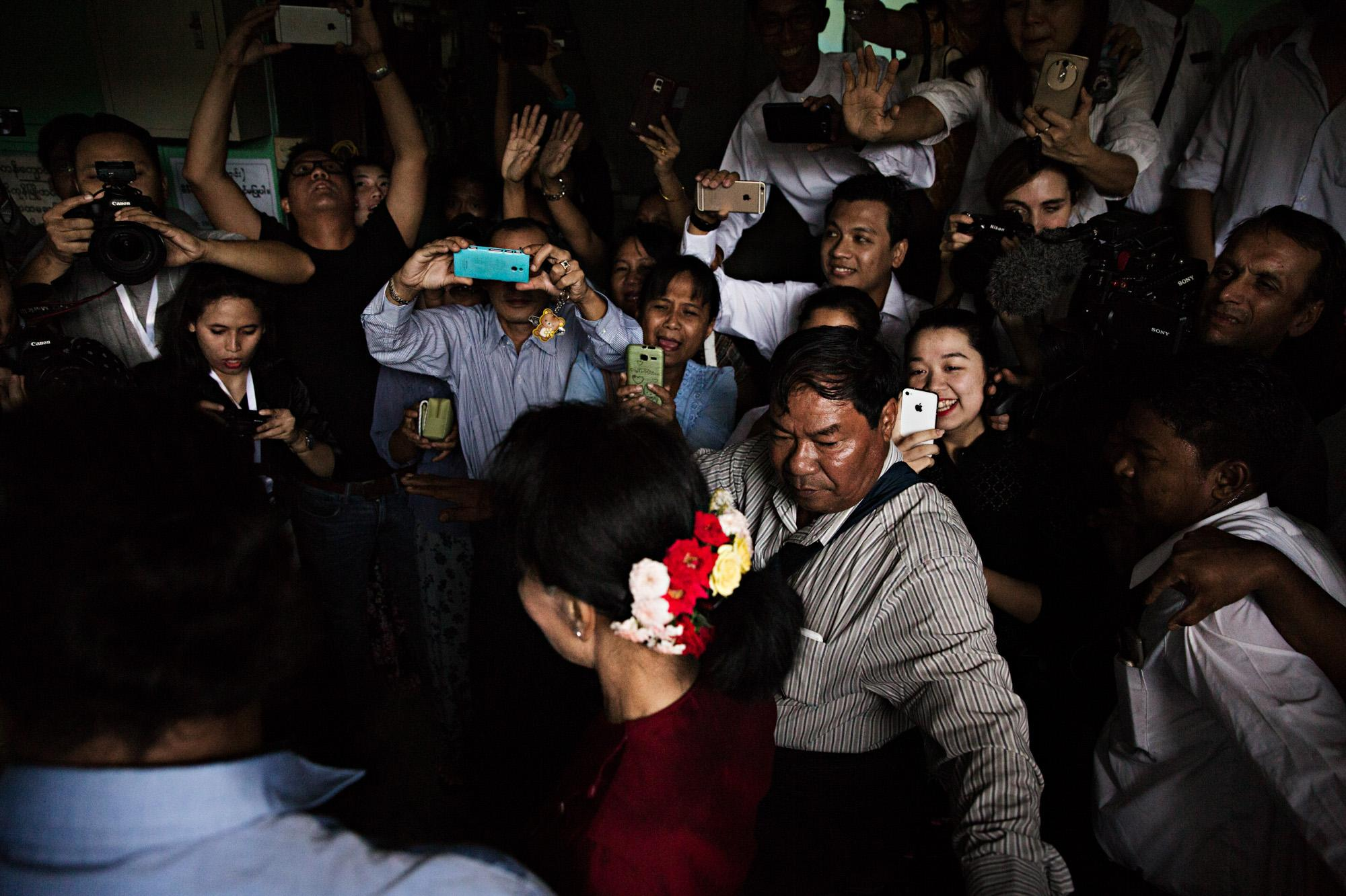 Aung San Suu Kyi (front, red flowers in hair) makes her way through a crowd after casting her vote in the historic 2015 election in Yangon, Myanmar.