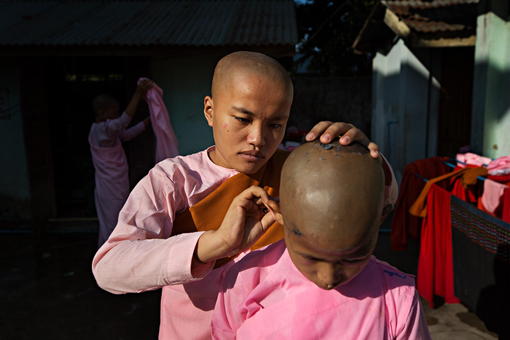 Novice Buddhist nuns shave their heads at a nunnery outside of Yangon, Myanmar. Shaving for the first time is a scary and vulnerable time for young nuns and they try to help each other through the experience. Nuns devote their lives to the Buddha's teaching just like monks, but do not have the same status enjoyed by their male counterparts.