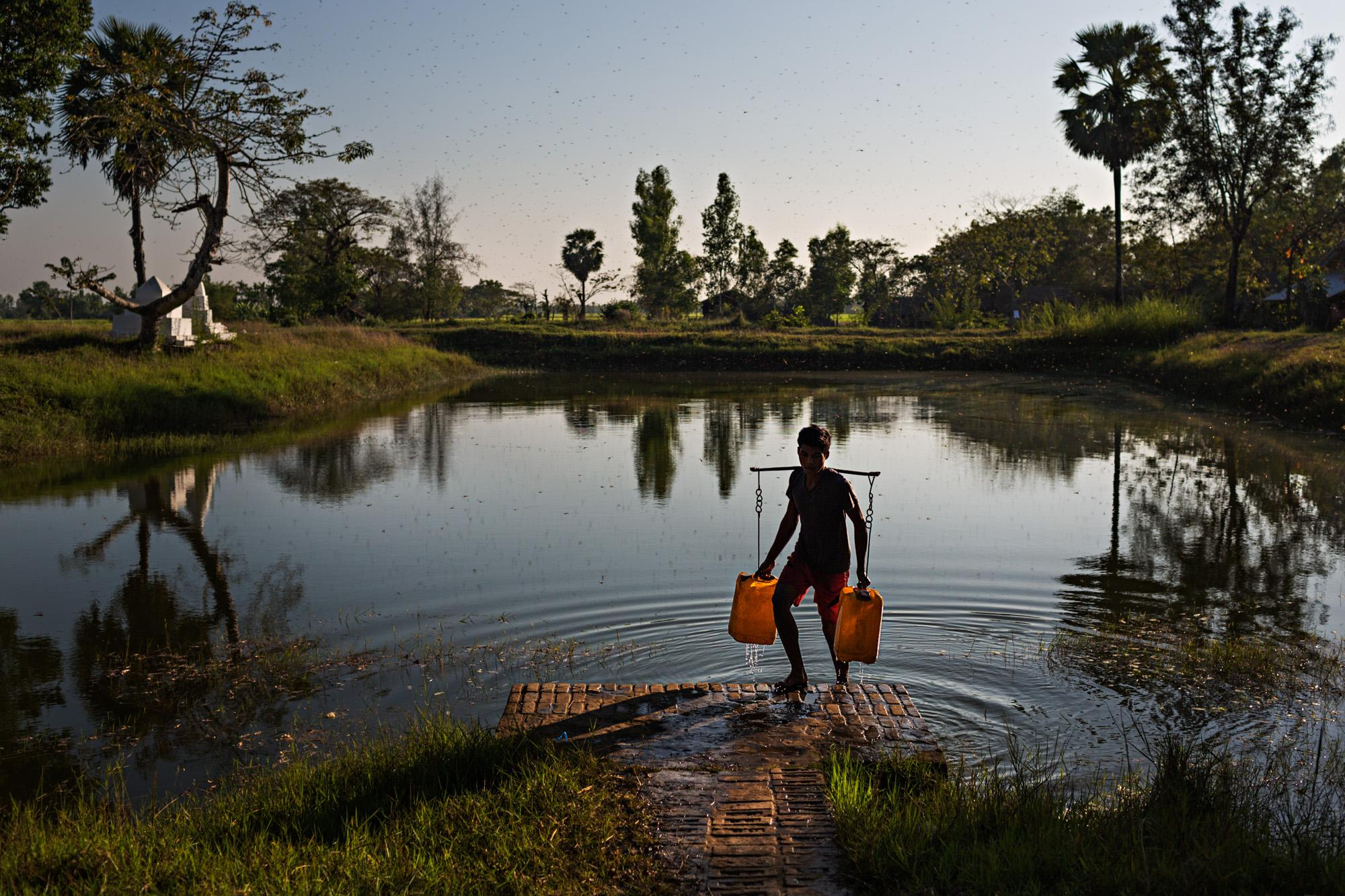 A boy gathers water from a community reservoir in a small farming village near to Pathein, Myanmar.