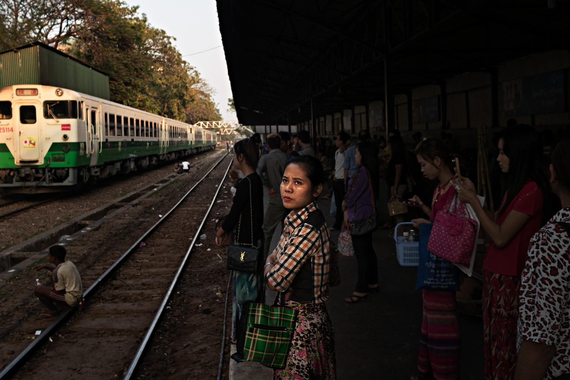 A woman waits for the train on her way home from work in Yangon, Myanmar.