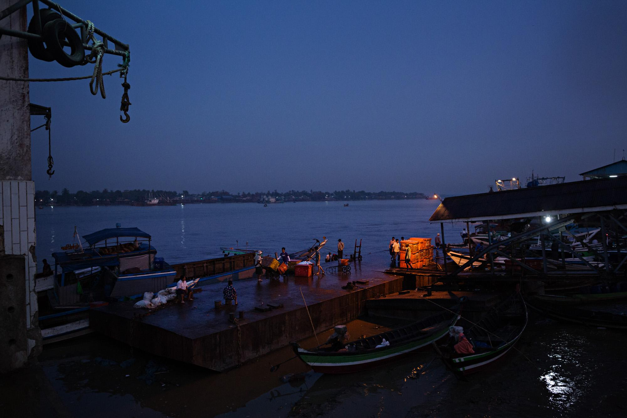 The first hints of dawn are seen over San Pya fish market in Yangon, Myanmar. This market is the main buying and selling point for shops, restaurants and individuals looking to purchase seafood and fresh water fish.