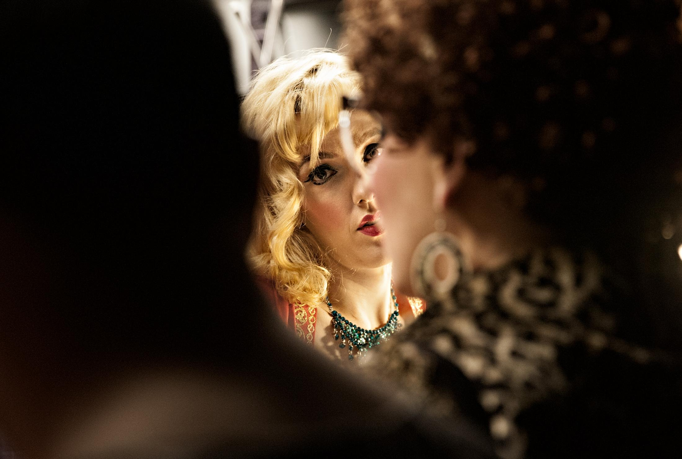 Red Hot Annie listens to a cast member while preparing for her show in the changing room.