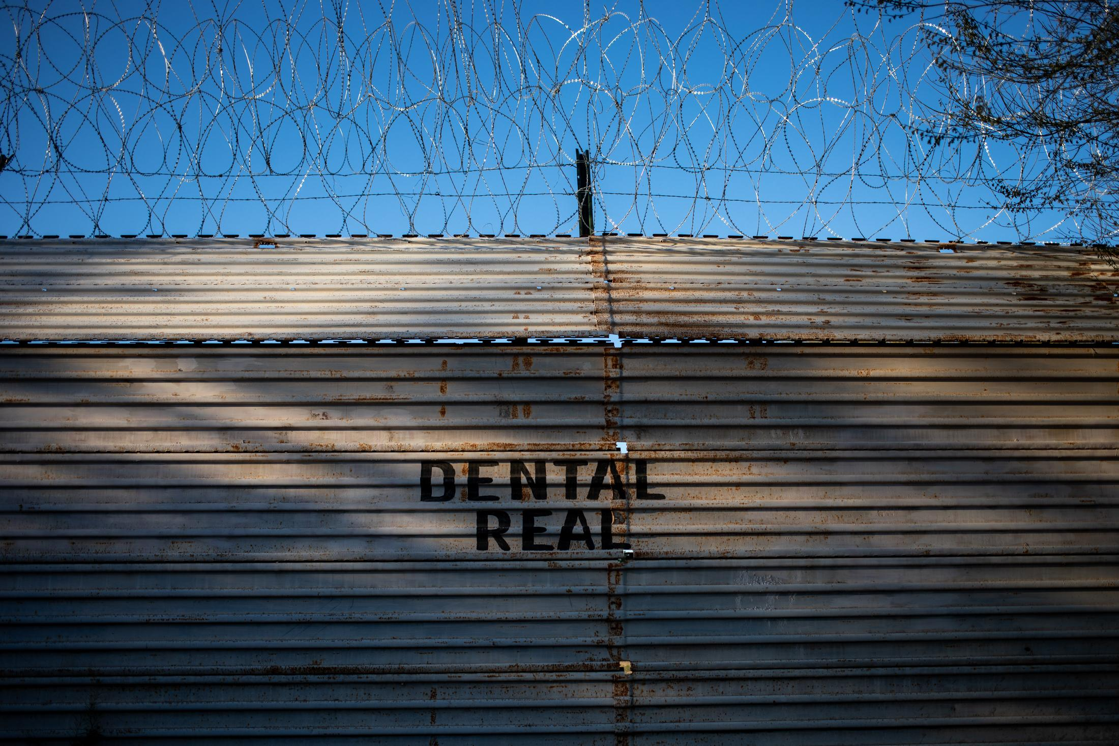 A sign for a dental clinic printed on the border fence between Mexico and Arizona.