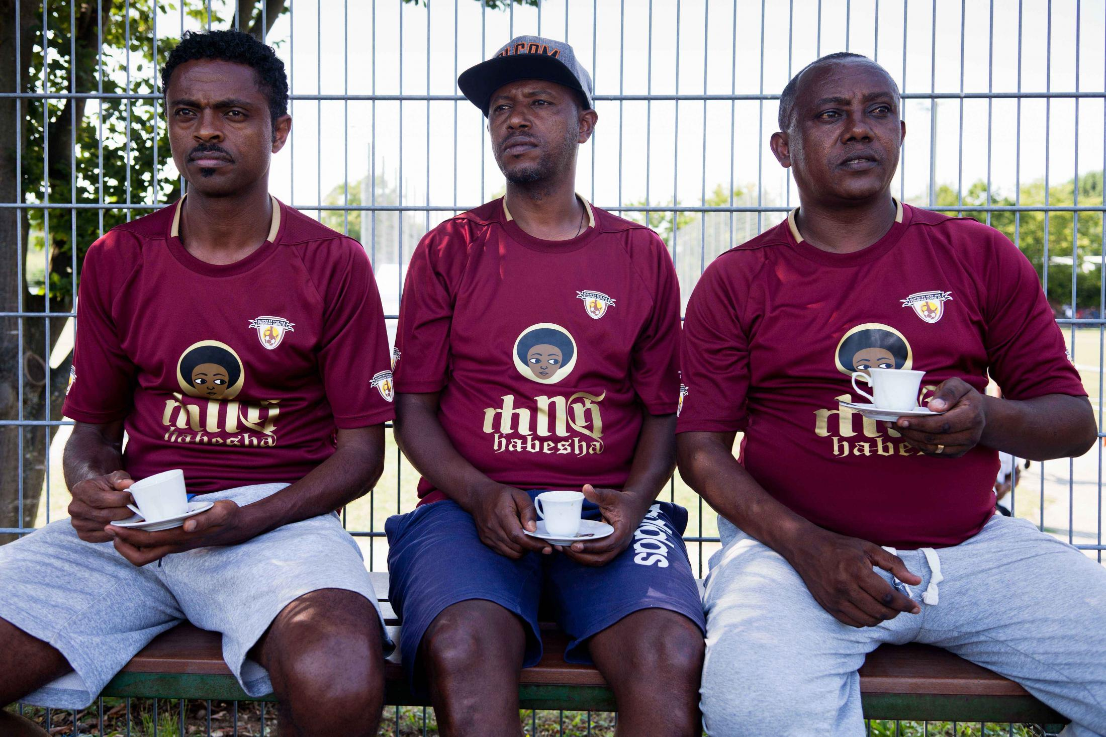 Three men watch the match whilst drinking traditionally prepared coffee. Their T-Shirts spell out the term Habesha,  used by Ethiopians and Eritreans to refer to themselves as one group, actively eliminating the differences between various tribes and celebrating the unity between the peoples.