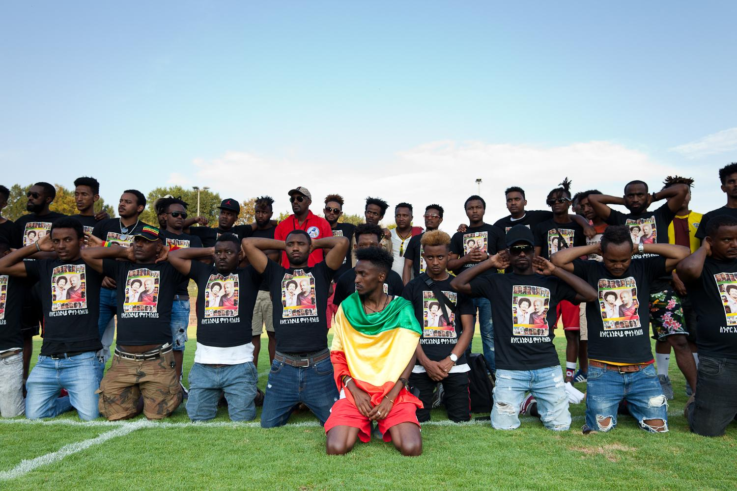 """During halftime of the final match, Amsalu (center) and others observe a minute of silence in memory of the family members and friends who have lost their lives during their escape. Over the last two decades, hundreds of thousands of Eritreans – around 12% of the entire population – have braved the official """"shoot to kill"""" policy at the borders to escape into either Sudan or Ethiopia and embarked on perilous journeys – risking predatory militias, exploitation, sexual violence and unforgiving tundra – with the aim of reaching Israel, the Gulf or Europe."""