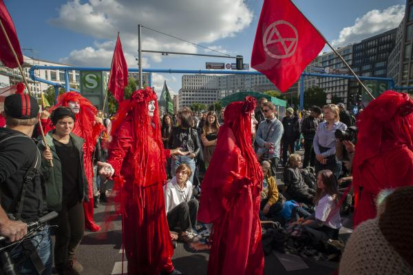 Red Rebels performance Art and Theatre. Extinction Rebellion take Potsdamer Platz, Berlin, Germany. A week of world wide protest against climate change and the inaction of governments globally to come to terms with the approaching disaster.