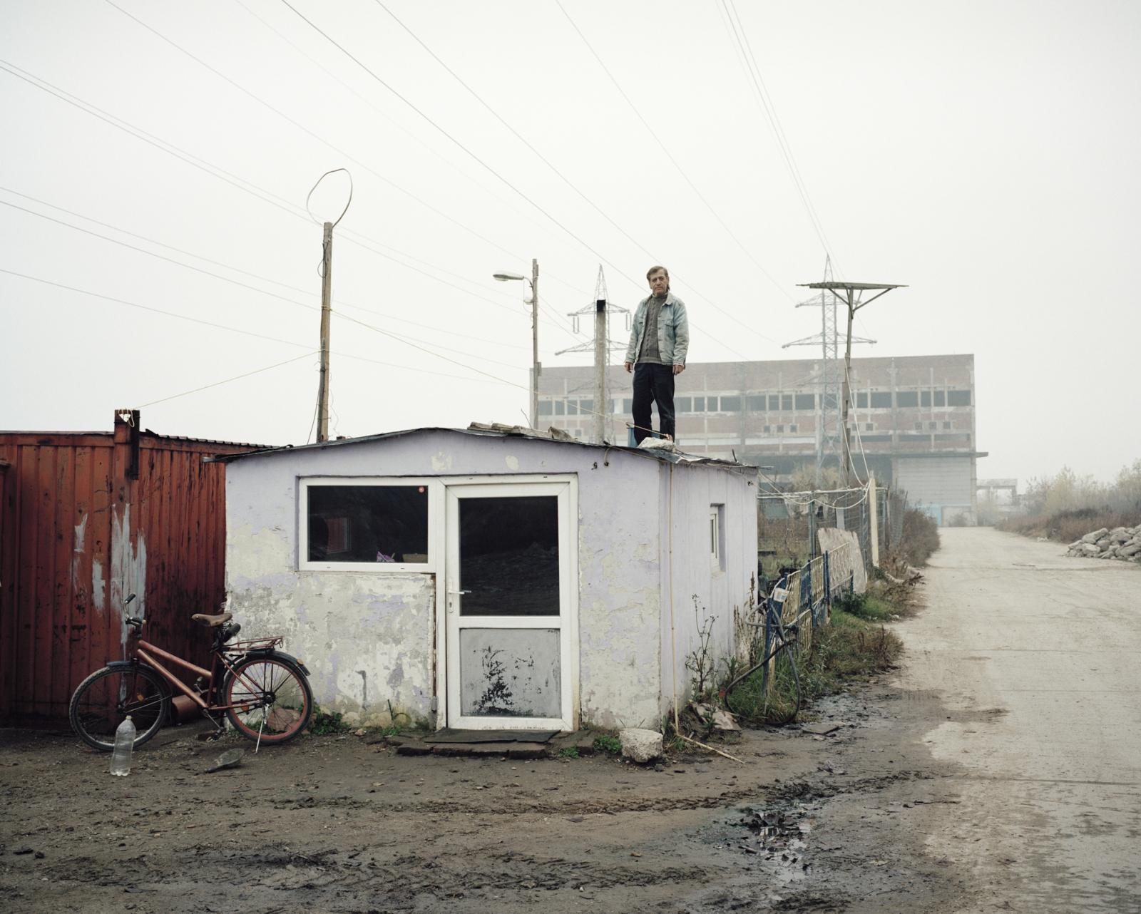 Romania, Giurgiu. A man working as security guard stand on a barrack in front of an abandoned factory that he watch.