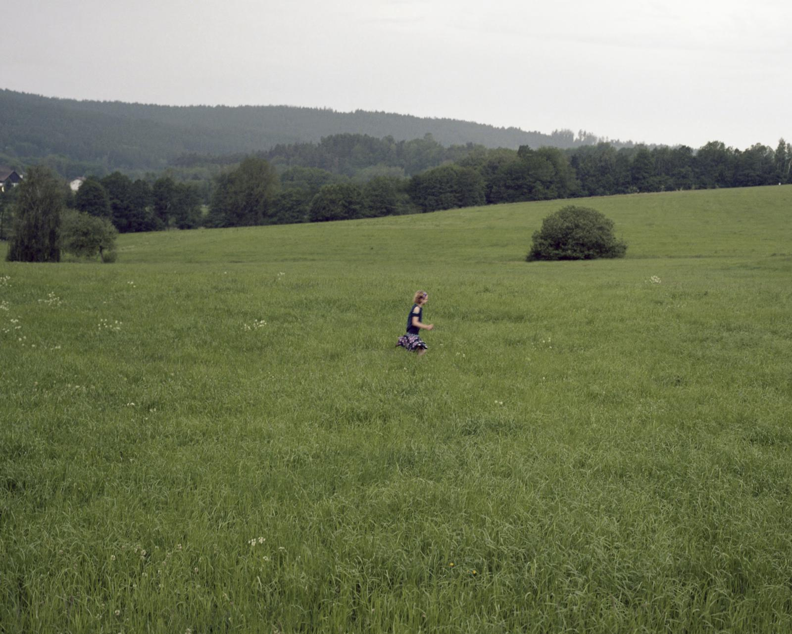 Germany, Bad Kotzting. A child run across a field during a religious procession.