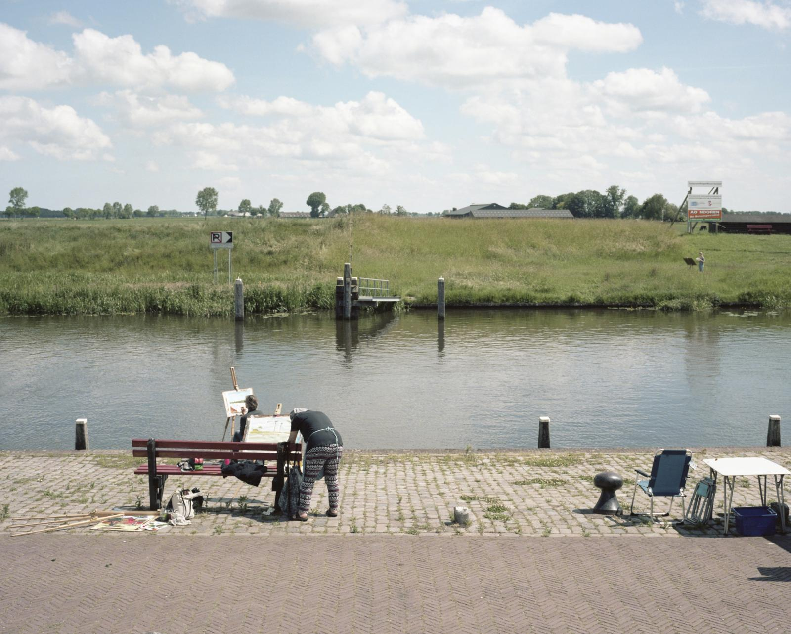 Netherlands, Garnwerd. People painting in front of a typical Dutch canal. The history of the Dutch canals is related to the construction of dykes used to obtain land from the sea, in fact most of the Netherlands is under the sea level. With the climate change and the rising of the sea level, Netherland is facing one of its biggest threats, despite the government is rising the dykes but several Dutch scientists are convinced that this won't be enough and that the country landscape will irreparably change with the rising of the ocean.