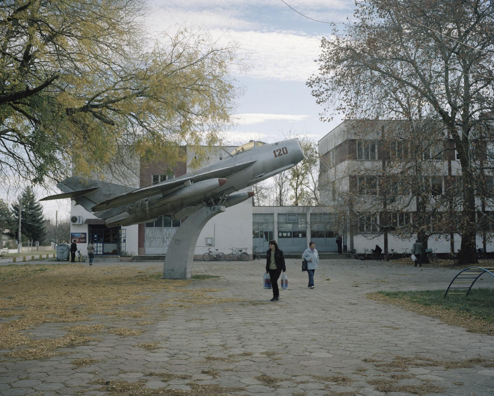 Bulgaria, Bardaski Geran. A MIG plane, Russian Cold War jet fighter aircraft in front of the Town Hall. In Bulgaria are still present several war-related monuments. These Russian Military monuments, standing in the places where they are displayed, are slowly deteriorated by the weather recalling an era that already ended. Most probably if tomorrow they would desassear the people wouldn't notice the difference.