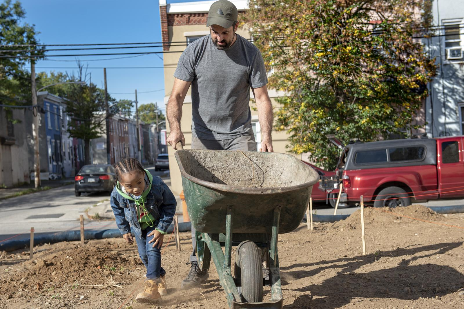 Christopher Parnell Jr., 6, left, and Teddy Pickering, 38, of Brewerytown Philadelphia, Senior studying Landscape Architecture at Jefferson University, right, work on building up a park on N 38th St., and Melon St. through the program Park in a Truck on Saturday, Oct. 12, 2019.