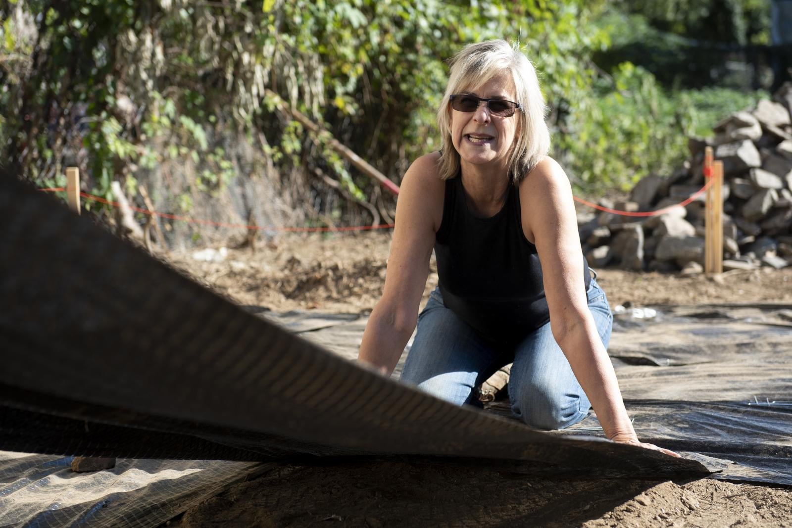 Kim Douglas, Director of Landscape Architecture and Associate Professor at Jefferson University, lays out a black mat to place gravel on for the construction of the park at the corner of N 38th St., and Melon St. through the program Park in a Truck on Saturday, Oct. 12, 2019.