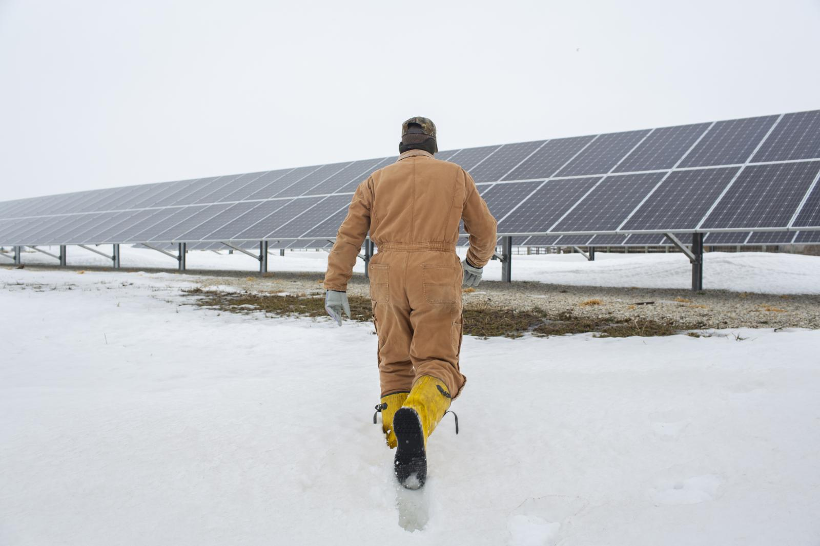 Randy DeBaillie walks toward solar panels at his farm in Orion, Illinois on February 3, 2019. Across the flatlands of Illinois, a new crop is rising among the traditional waves of grain. Hundreds have applied to host acres of solar panels on their property, a move encouraged by a state requiring that renewable resources provide 25 percent of Illinois power by 2025.