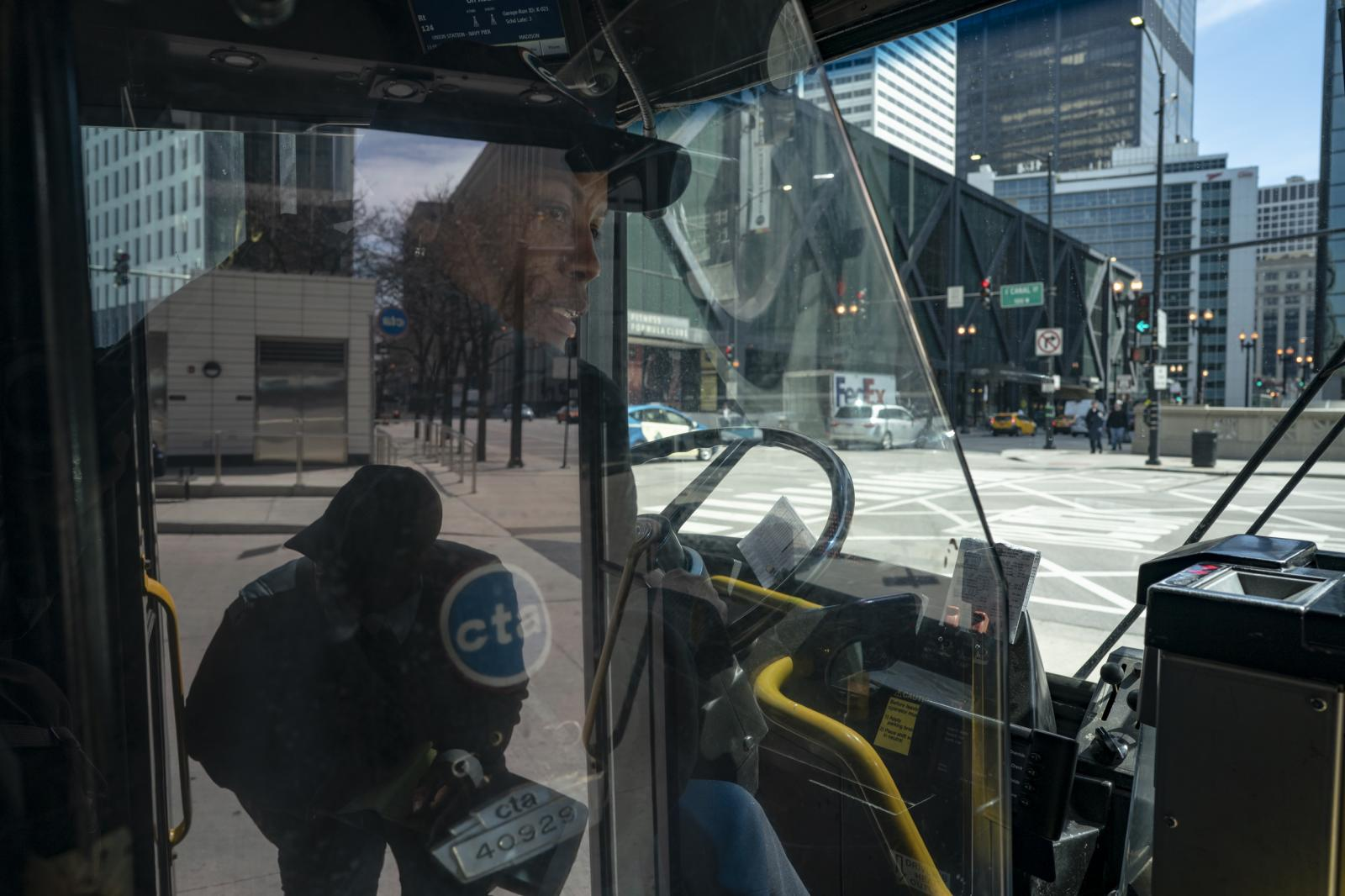 Bus driver Lorrie Lackland checks in with a Chicago Transit Authority agent before driving the 124 bus in Chicago, Illinois on April 25, 2019. Lackland has driven buses in Chicago for 14 years.
