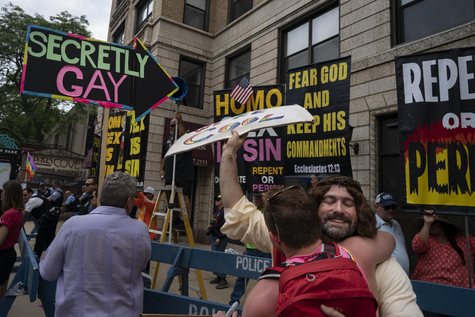 "Scott Whitehair, dressed as Jesus Christ, gives out free hugs to counter-protest a Christian hate group during Chicago's 50th Pride Parade on June 30, 2019. ""I showed up because it's a chance to make people laugh and smile when they walk by instead of hearing these terrible stuff,"" Whitehair said."