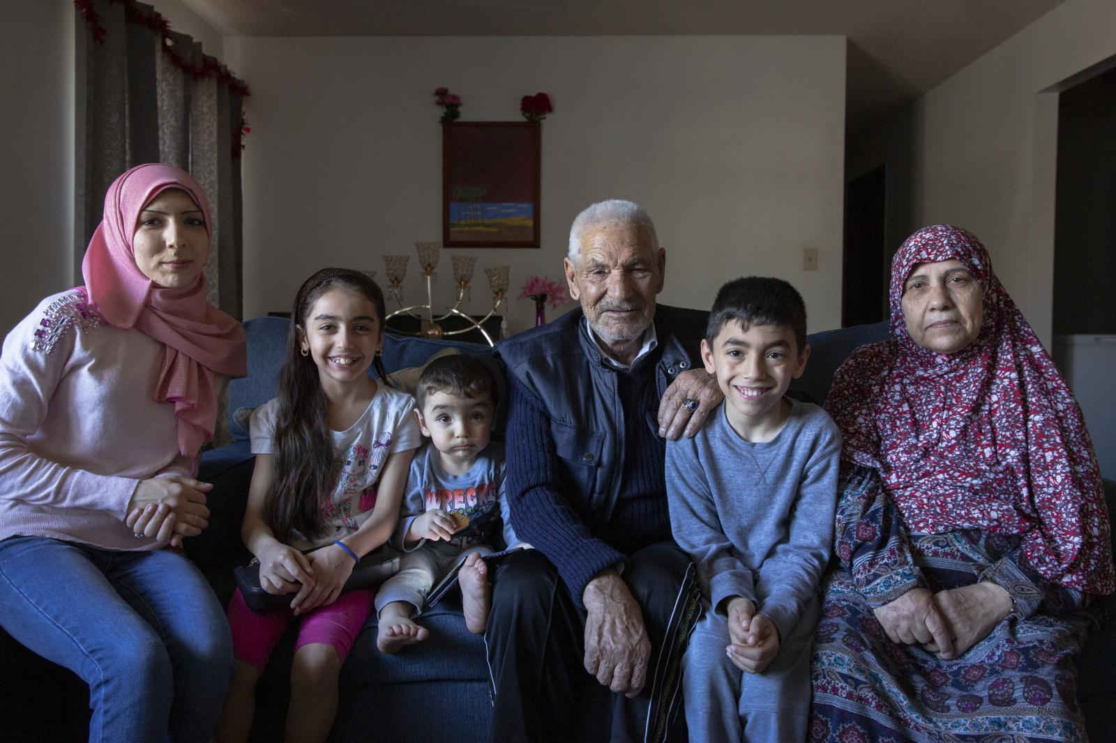 Khaled Assaf and his wife Mariam Rastanawi with their daughter and grandchildren at home in Indianapolis, Indiana on March 26, 2019. The couple arrived in the United States as Syrian refugees after years of waiting. They are two of the lucky few, as the United States has all but stopped allowing Syrian refugees into the country.