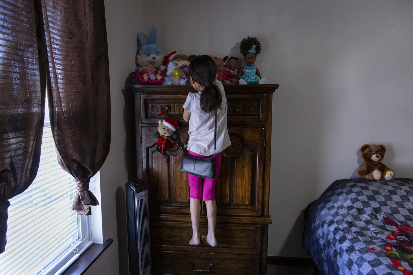 "Intisar Bakour, 8, reaches for her favorite doll in her room in Indianapolis, Indiana on March 26, 2019. Bakour said she felt nervous meeting with her grandparents at the airport for the first time since she was four, and she didn't recognize them at first. ""And then my mom told me that was her mom and dad, and then I knew they are my real grandparents."""