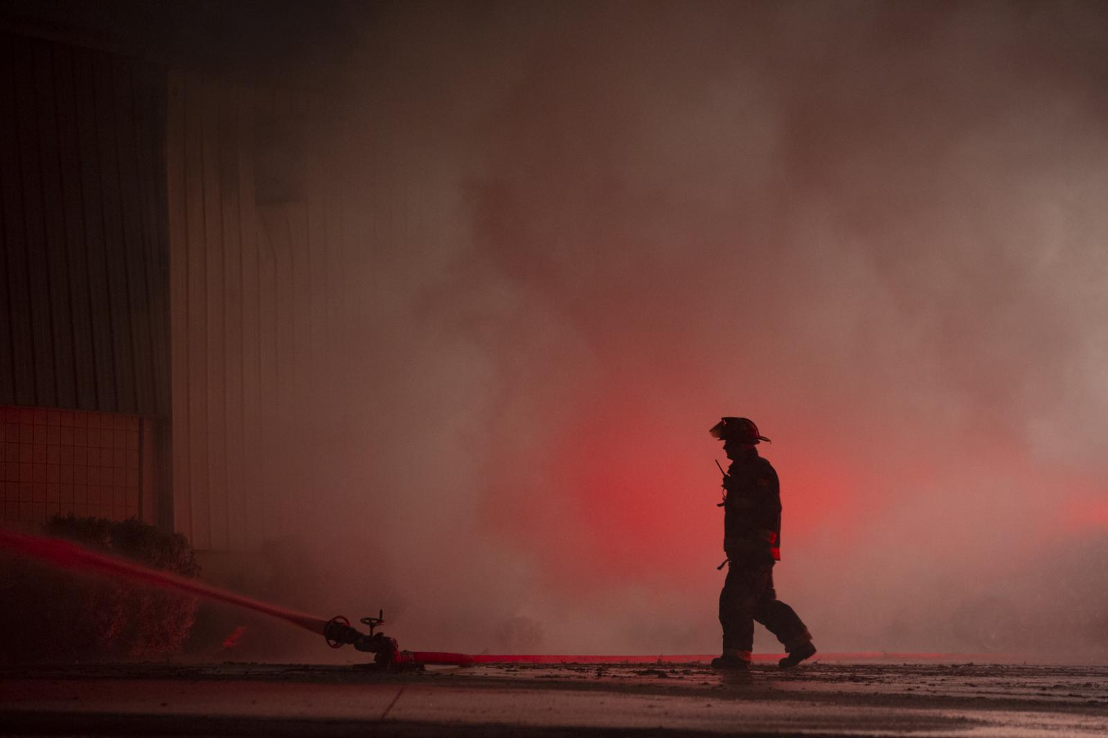 A firefighter monitors a hose as crews from multiple departments battle a large fire that broke out over night at Muskegon Casting Corporation at 2325 S. Sheridan Dr. in Muskegon, Mich. on March 15, 2017. Muskegon Public Safety Director Jeffrey Lewis said an estimated 40 employees evacuated safely from the fire, which is believed to be caused by an equipment malfunction that created a spark to combustibles in the foundry, which is full of oils and metallurgic dust.