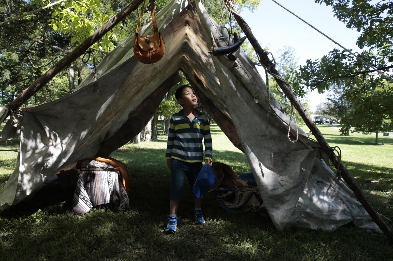 "Lucas He, 8, explores a 19th-century-style mountain man camp during Columbia's 39th annual Heritage Festival and Craft Show at Nifong Park on Sept. 17, 2016. A dozen artisans and tradesmen dressed in 19th-century attire demonstrated their trades and sold their wares. Xiao Ling Guo, the boy's mother, said, ""We are newcomers, so I think it's really important for us to understand the depth of local culture."""