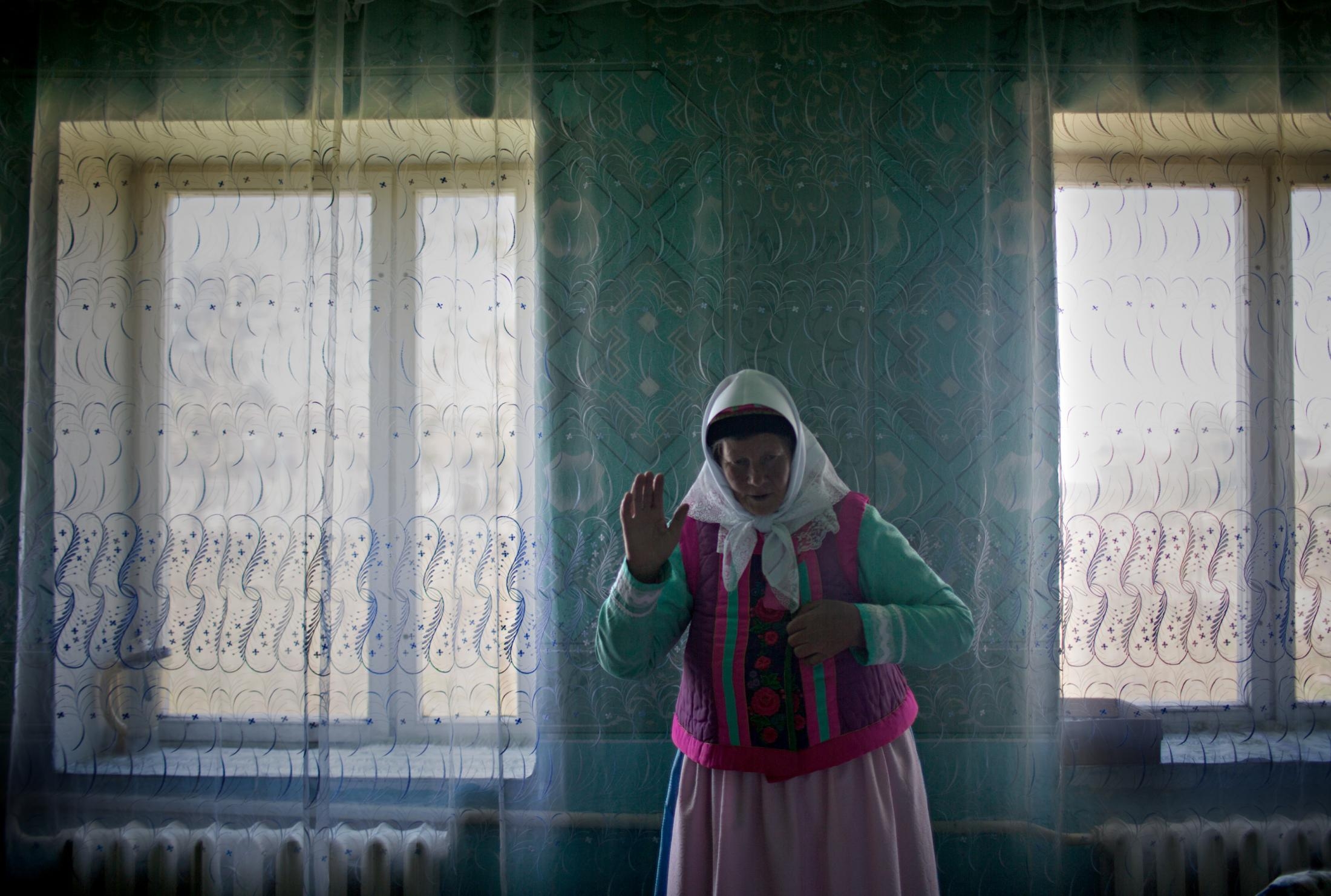 A Doukhobor woman shows off her traditional clothing. The Doukhobors are peaceful and their homes are painted with joyful shades of green, blue and white.