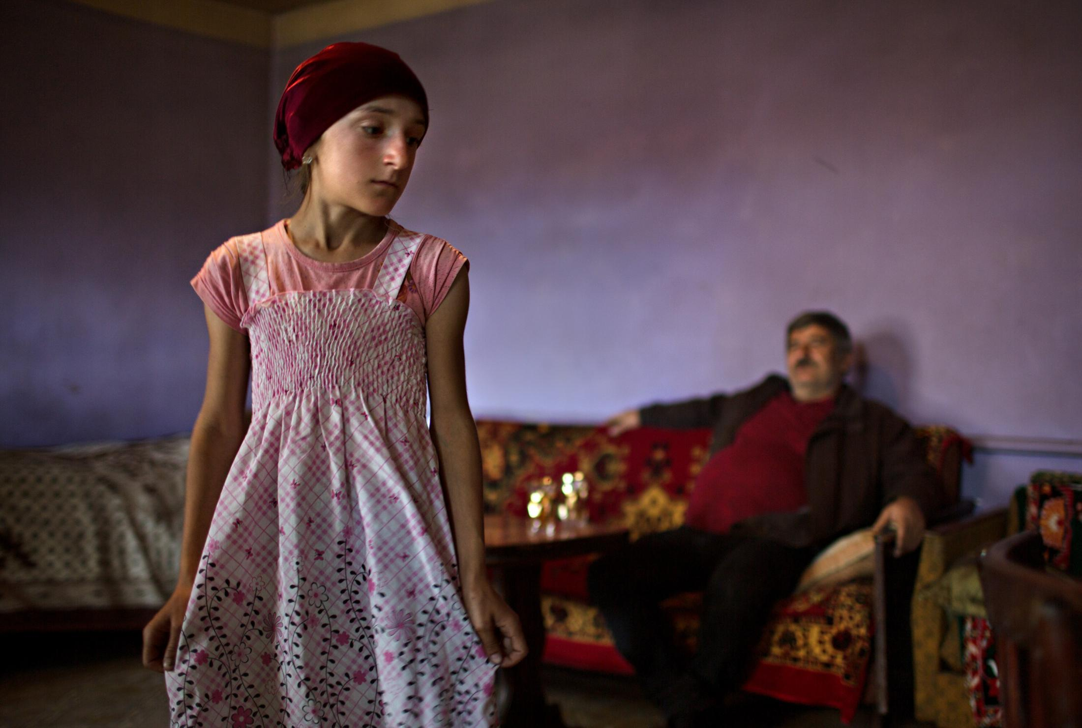 A young Muslim girl shows off her dress under the watchful eyes of her uncle.