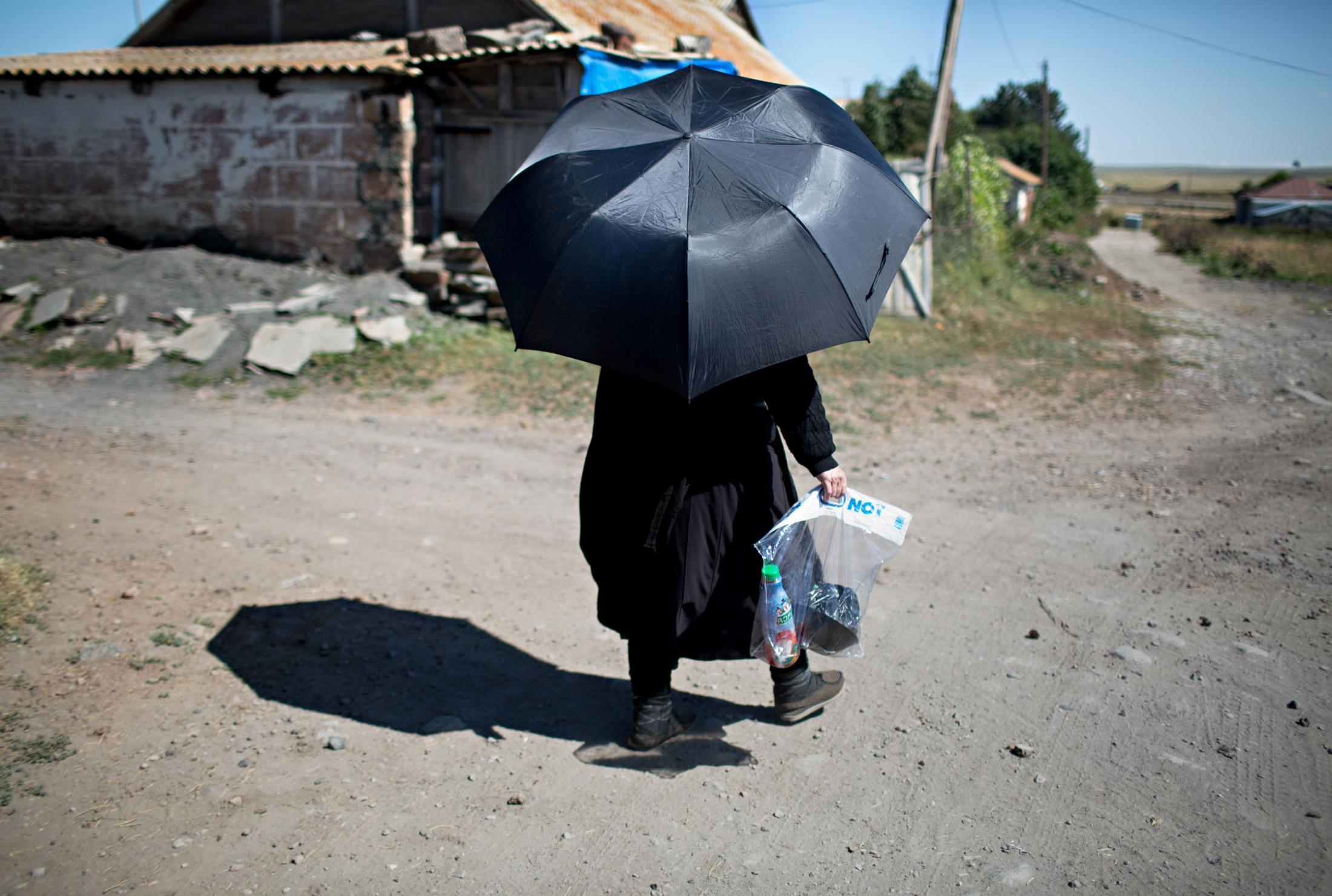 A Muslim woman returns from shopping while protecting herself against the sun with an umbrella.