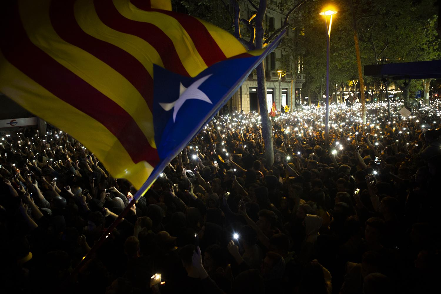 A pro-independence Estelada flag is waved above demonstrators holding up their cellphones during a protest in Barcelona, Spain, Tuesday, Oct. 15, 2019. Spain's Supreme Court on Monday convicted 12 former Catalan politicians and activists for their roles in a secession bid in 2017, a ruling that immediately inflamed independence supporters in the wealthy northeastern region. (AP Photo/Joan Mateu)