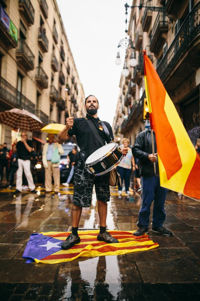 A man with neo-nazi tattoos stands on a catalan flag during a unionist and nationalist demonstration in Catalonia. September 30th, 2017