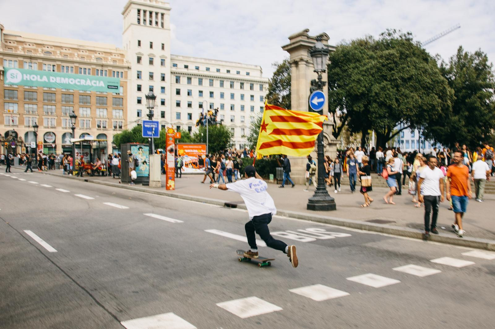 A skater blasts around Barcelona with a Catalan flag. October 2nd, 2017