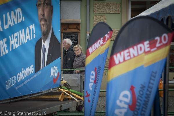 Locals walk by the AfD 'Family Festival' political rally in Gotha, Thuringia, Germany.