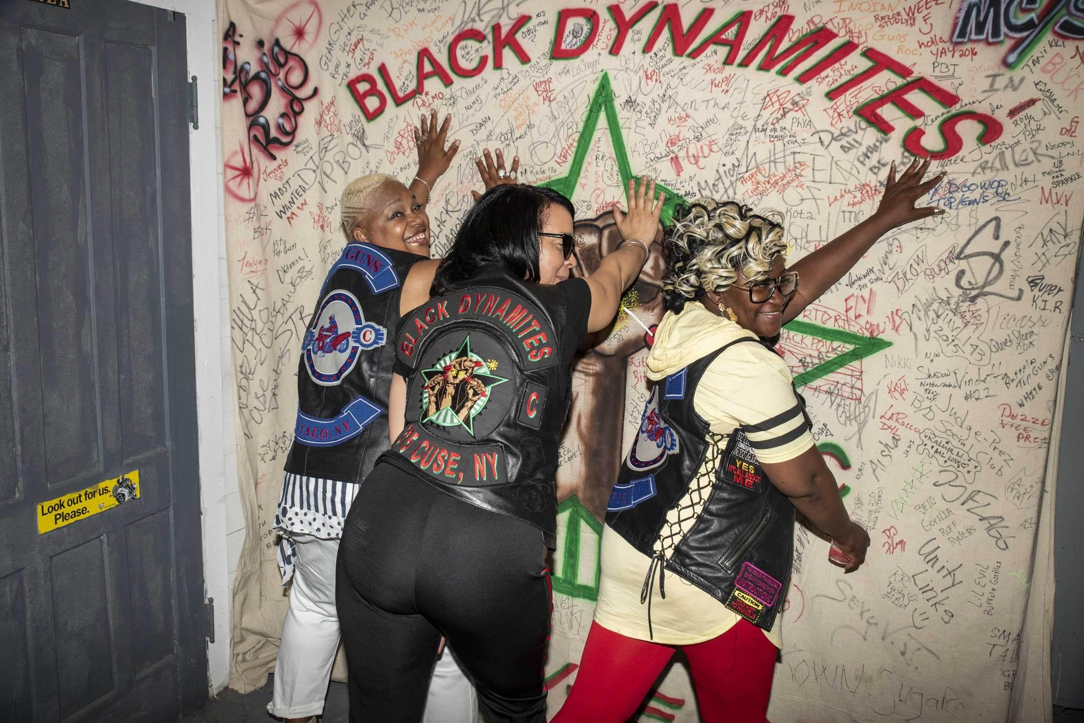 """Top Guns and Black Dynamites social club members Nice Nasty, Redbone, and Shorty Doowop gather for a party, posing in front of a tapestry signed by all who are invited to the Black Dynamites' hangout """"The Bottom."""""""