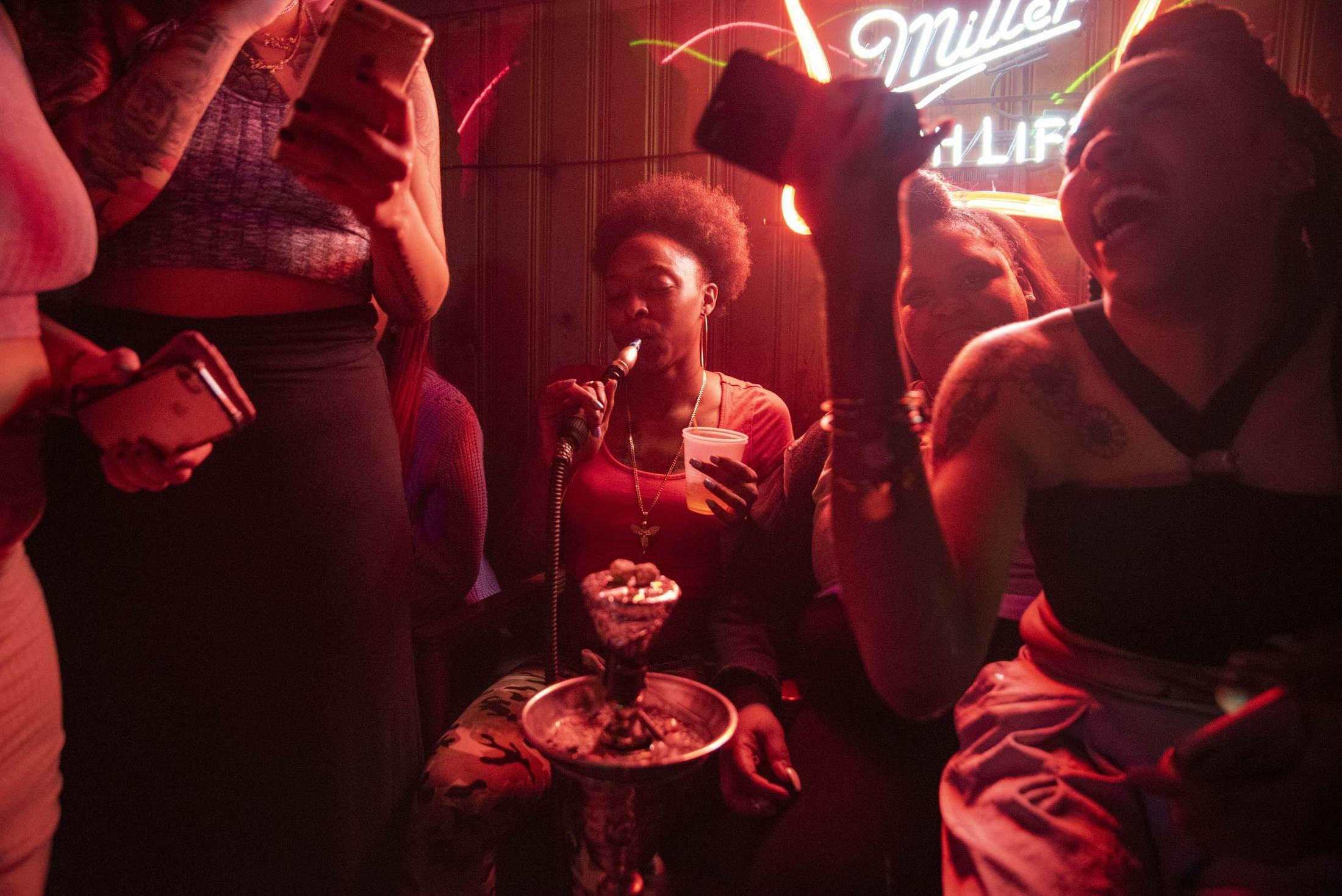 """Oriana Kyles (center) at """"the hooka spot,"""" an underground hangout in the basement of a convenience store, is one of Syracuse's best-kept secrets, hosting some of the greatest parties in town before shutting down when it became too popular."""