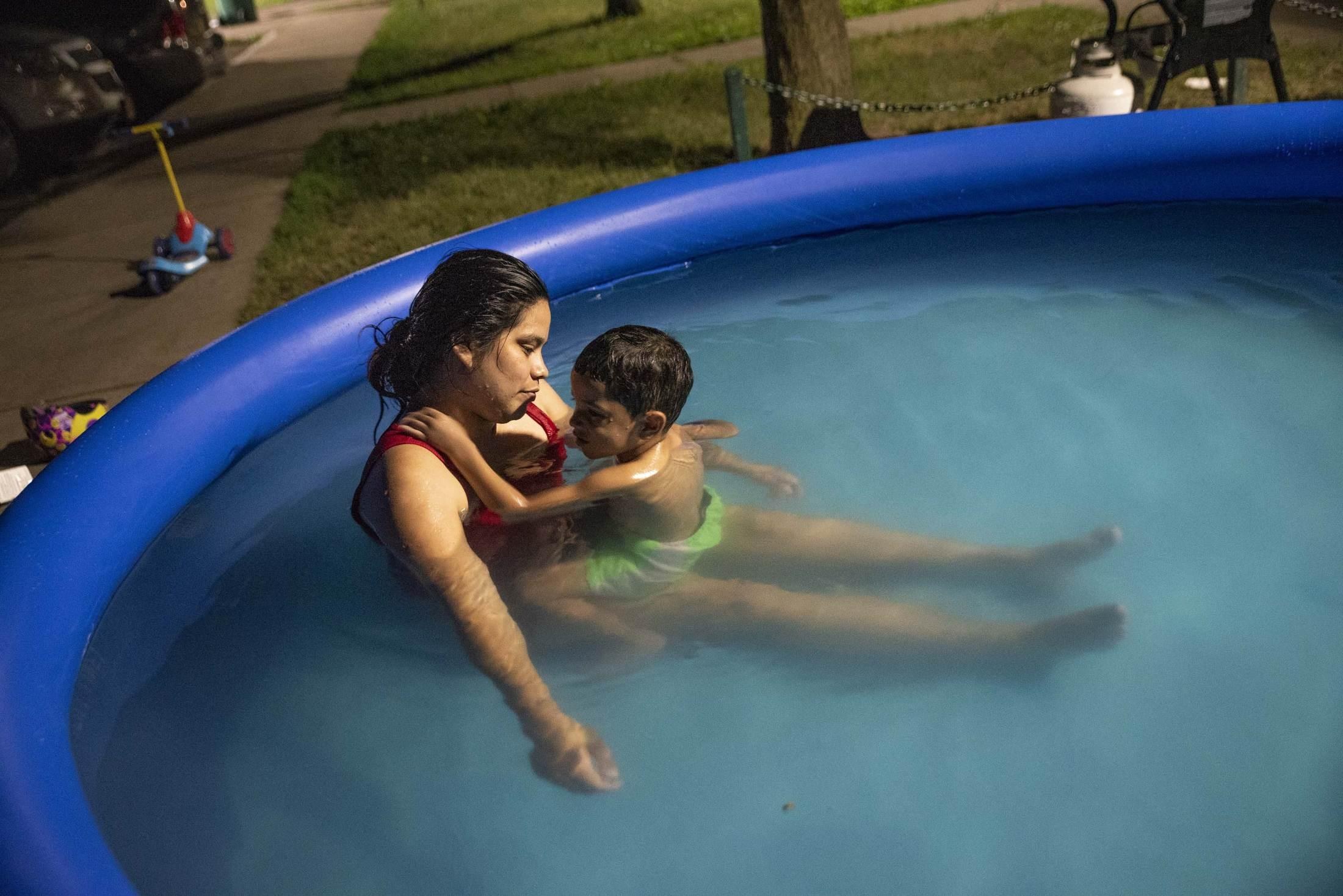 """A series of 90-degree days spill into the comfort of night as the high temperatures bake the city of Syracuse. Carla and her son Jaxiel """"Che Che"""" seek relief with an evening swim."""