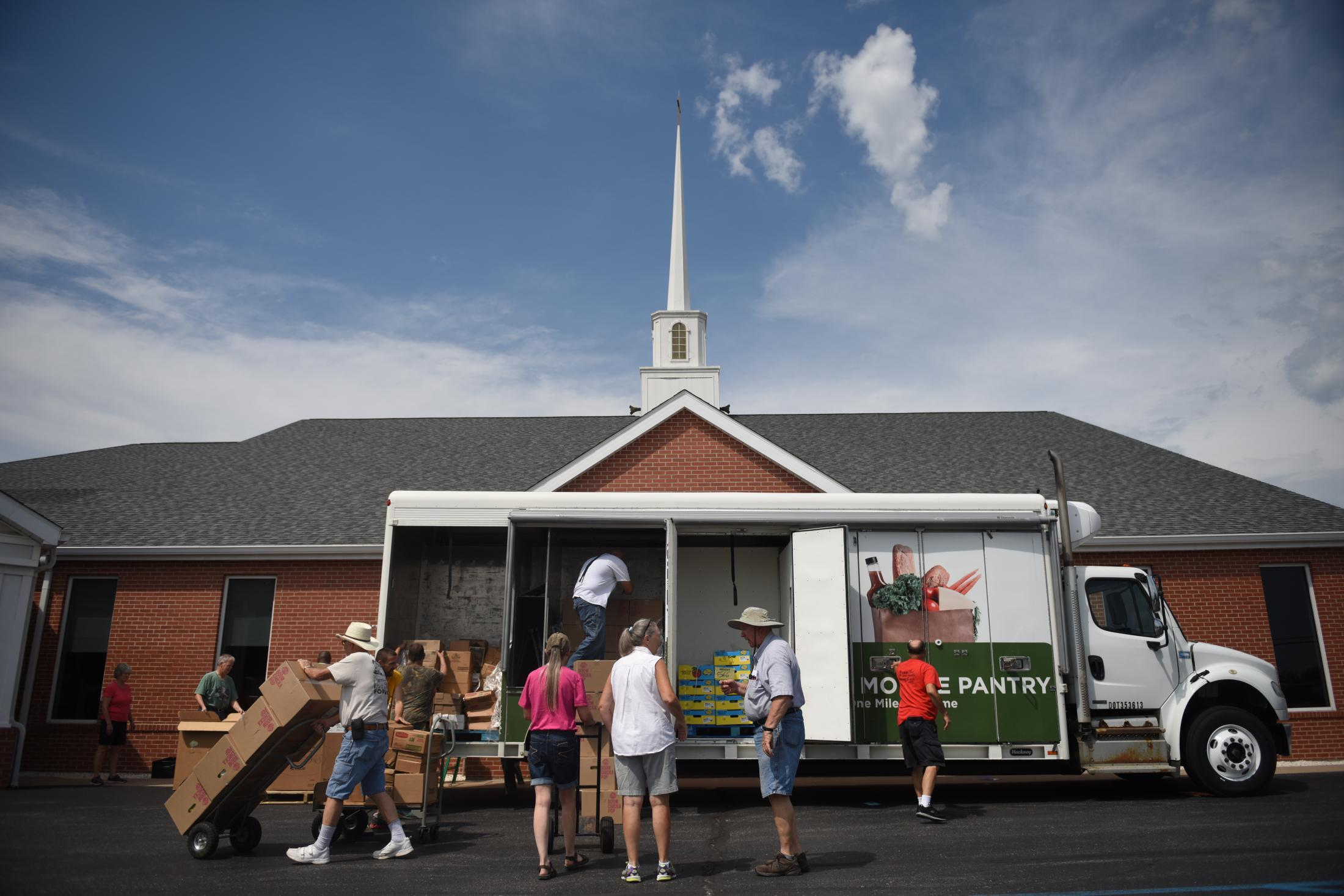 Volunteers at Ashland Baptist Church unload food delivered by The Food Bank for Central & Northeast Missouri truck Aug. 20, 2019 in Ashland, Missouri. The church hosts a drive-thru food bank for those in need every third Tuesday of each month.