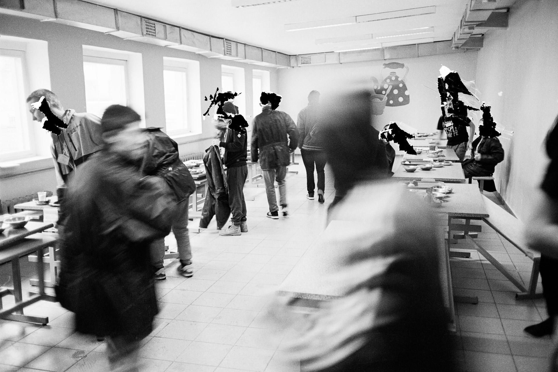 In the dining hall, the prisoners are separated into two groups: those serving their sentences eat in one room, those in remand detention in the other. With the permission of a guard who escorted me at all times, I went to the dining hall to photograph it. A group of youth came in and sat down at the tables, each with his own designated spot. They took advantage of my presence to quickly explain to me that their meals were never good. I took two photos and another guard raced to stop me. I understand that each guard enforces the rules a bit as he interprets them. The administration will have the last word: it orders me to scratch out the identities of each inmate. A la cantine, les prisonniers sont séparés en deux groupes : ceux purgeant leur peine déjeunent dans une salle, ceux en détention provisoire dans l'autre. Le quotidien des détenus m'intéressait évidement. Un jour, j'avais demandé au garde qui m'accompagnait en permanence si je pouvais photographier la cantine. Avec son accord, on y est allé. Un groupe de jeunes arrive alors pour s'attabler. Chacun possède sa place attitrée. Ils profitent de ma présence pour m'expliquer rapidement que leur repas n'est jamais bon. Je fais deux photos et très vite, un autre garde se précipite pour m'interpeller. Je comprends que chaque surveillant applique les règles un peu comme il l'entend. Mais finalement, plus tard, ce sera le service de sécurité qui aura le dernier mot, en m'ordonnant de gratter les identités de chaque détenu. © Jérémie Jung