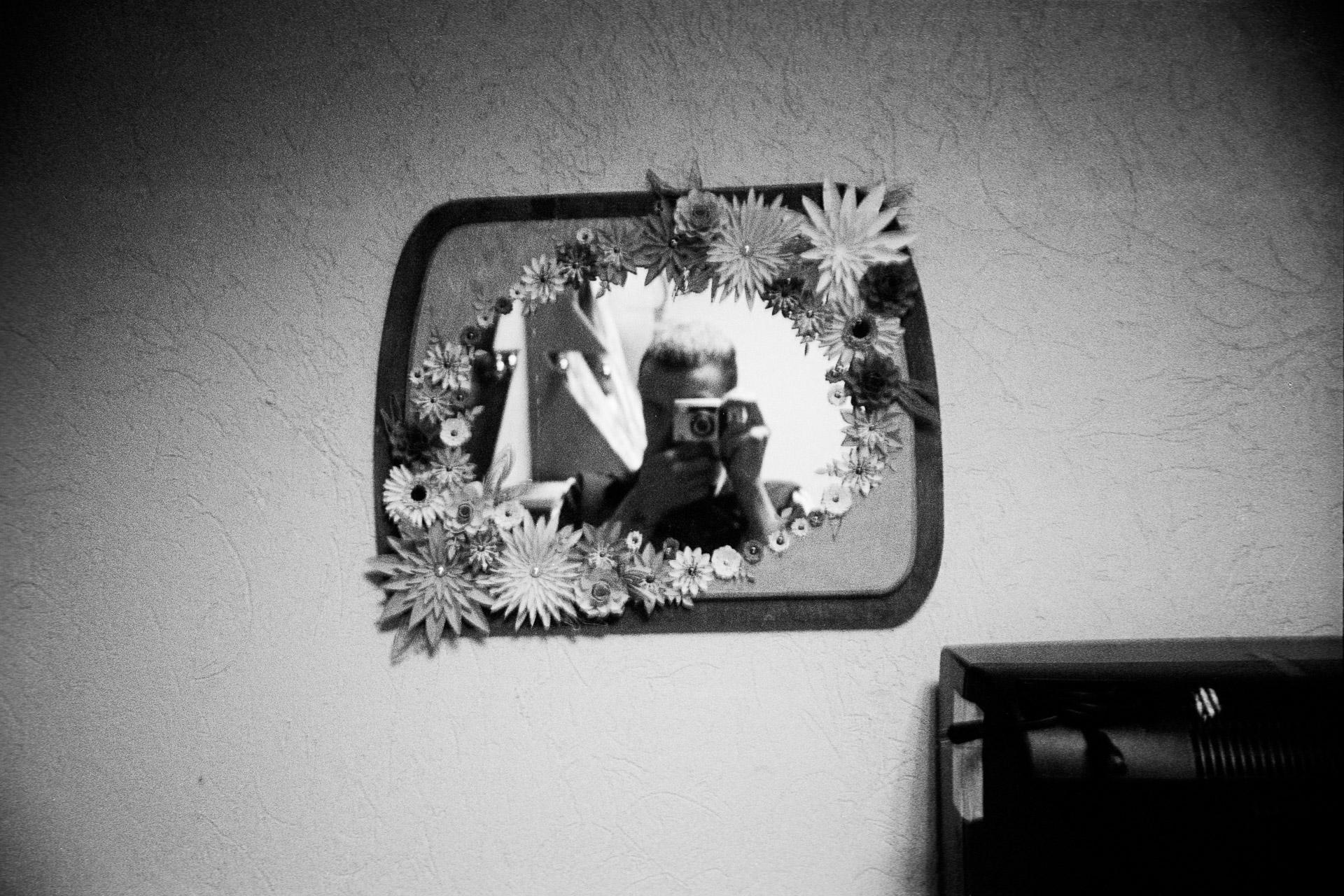 In a common room, A. takes a photo of himself in a mirror. He crafted the flowers from paper with his own two hands before using them to decorate the mirror. Ici, dans une salle collective, A se prend en photo dans un miroir qu'il a lui même décoré de fleures en papier également confectionnées par ses soins durant son temps libre. © A / Jérémie Jung