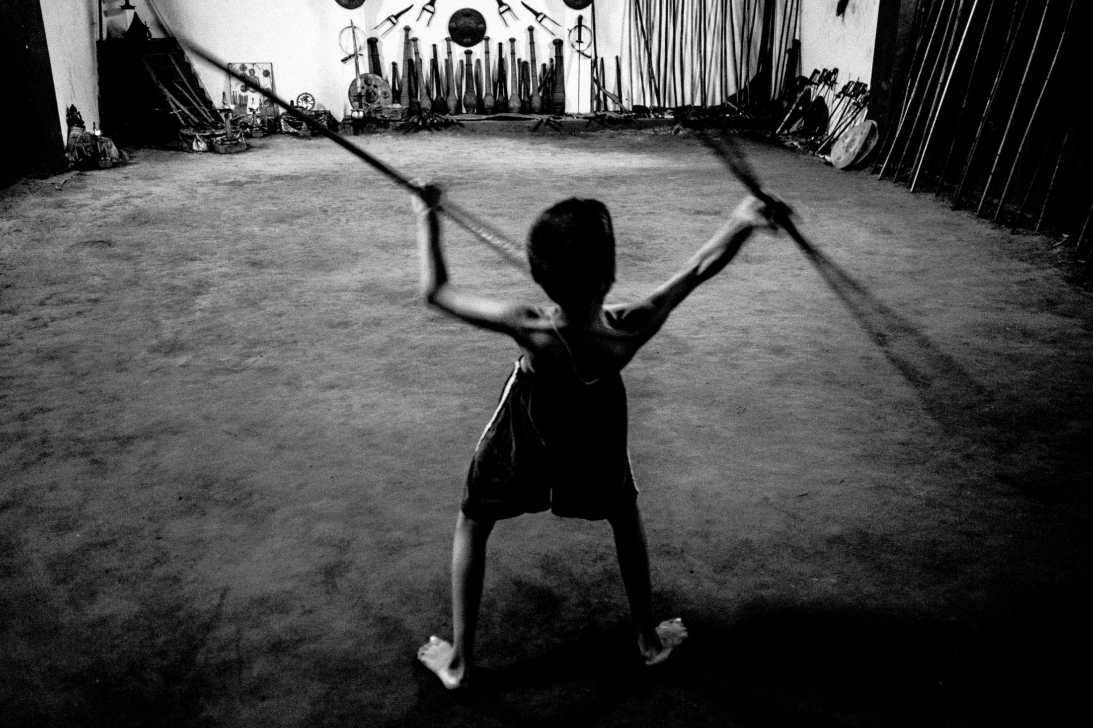 A child does coordination training with the help of two bamboo sticks while waiting for his master.