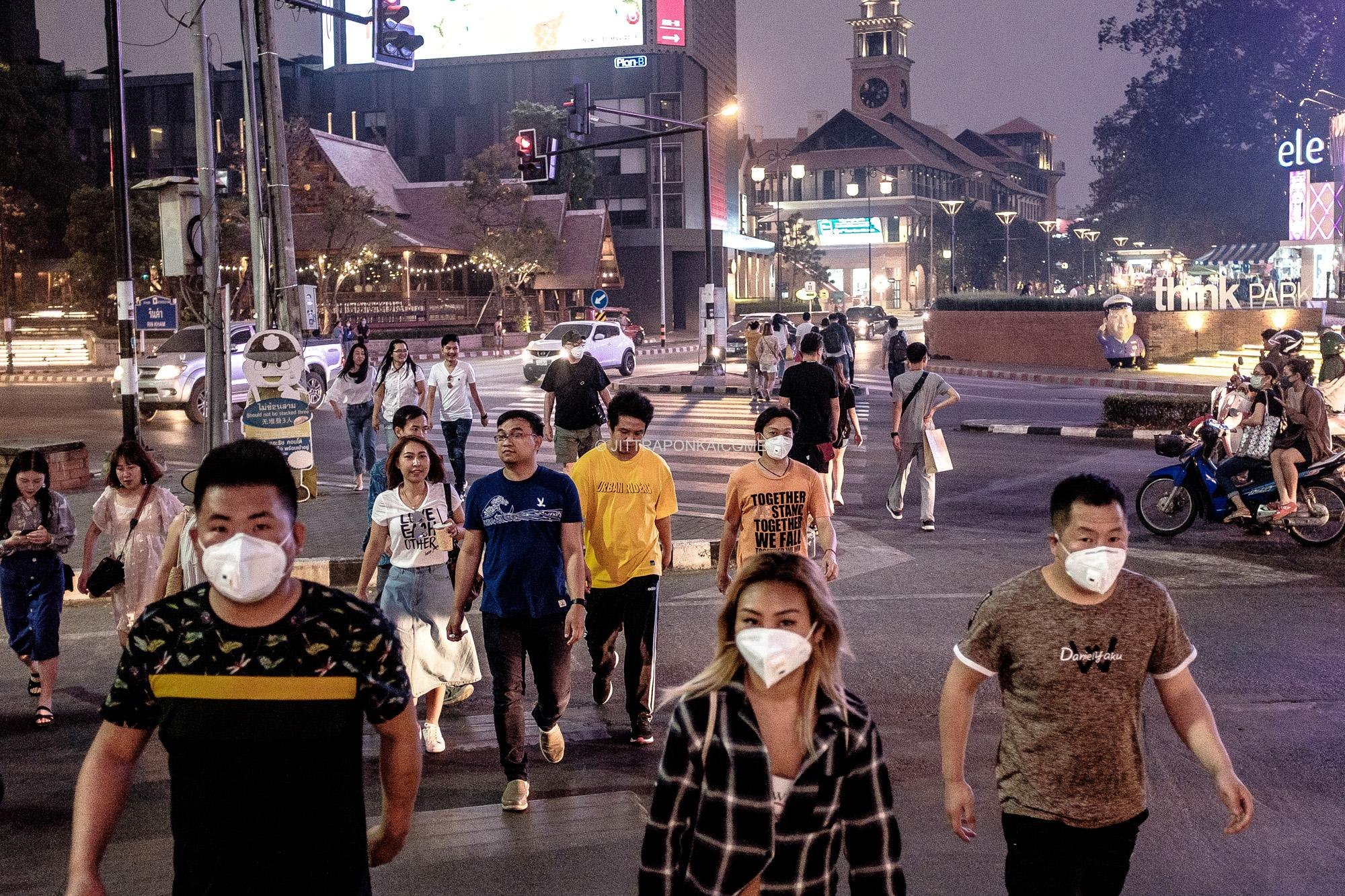 The Chiang Mai sky is covered all over by smoke. Locals and foreigners alike are affected by heavy smog. People are seen walking in the evening across the Rin Kham intersection of Suthep and Nimmanhaeminda road. This is one of the locations in Chiang Mai that has economic importance, due to its trendy shops, restaurants, cafes, and galleries.