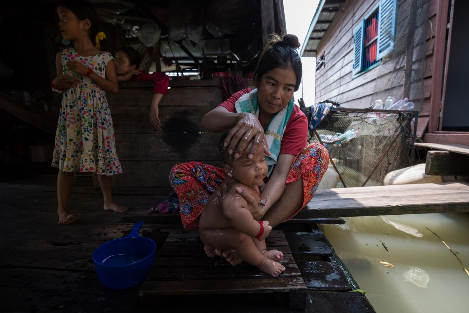 Ms Hourn washes her baby on their floating house in Prek Toal village on the Sangkaé River. Because of the remote location of her village any serious health issue that must be dealt with by a hospital involves a 40 minute boat ride followed by a 30 minute trip down dusty Cambodian roads. Siem Reap Province, Cambodia - October 2019