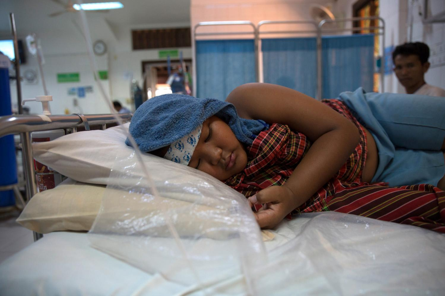 Chan Pheakdey, 10, lies in bed a hospital bed in the inpatient ward of the Angkor Hospital for Children suffering with Dengue hemorrhagic fever. His mother, sister and neighbours all caught dengue fever this year putting a huge burden on an already poor family. Siem Reap, Cambodia - October 2019