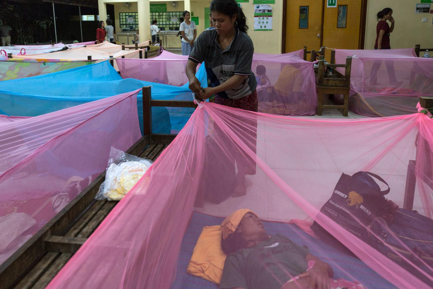 For those patients who travel long distances to visit the Angkor Hospital for Children, they are allowed to sleep on premises. As night falls mosquito nets are given out to everyone who will set them up outside the main hospital building. Siem Reap, Cambodia - October 2019