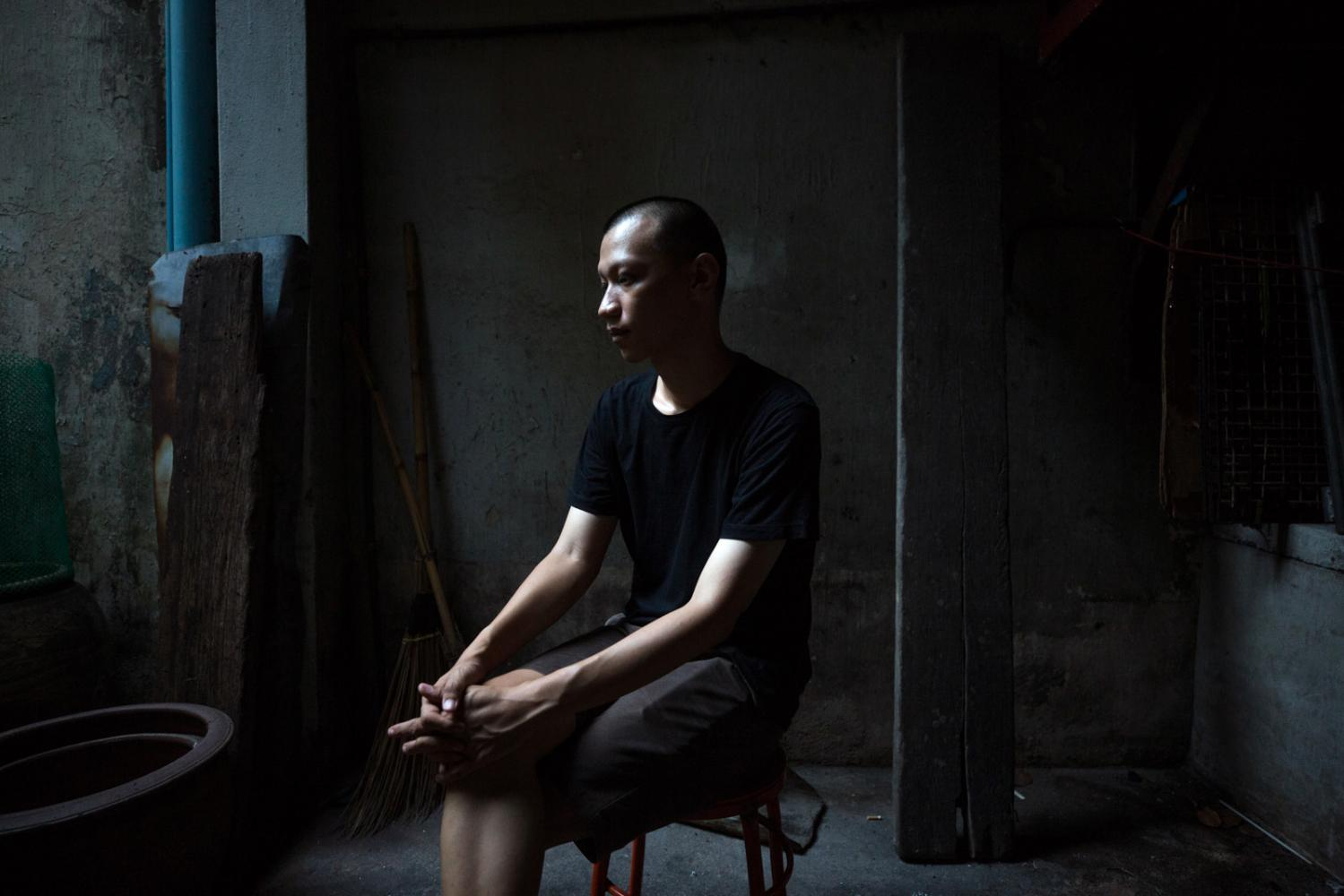 Jaturang Wongjiragorn, 28, sits in the dark alleyway outside his house in Chinatown, Bangkok. In September 2019, 4 members of his family caught dengue fever of which his father died from the disease after several misdiagnoses. Bangkok, Thailand - October 2019