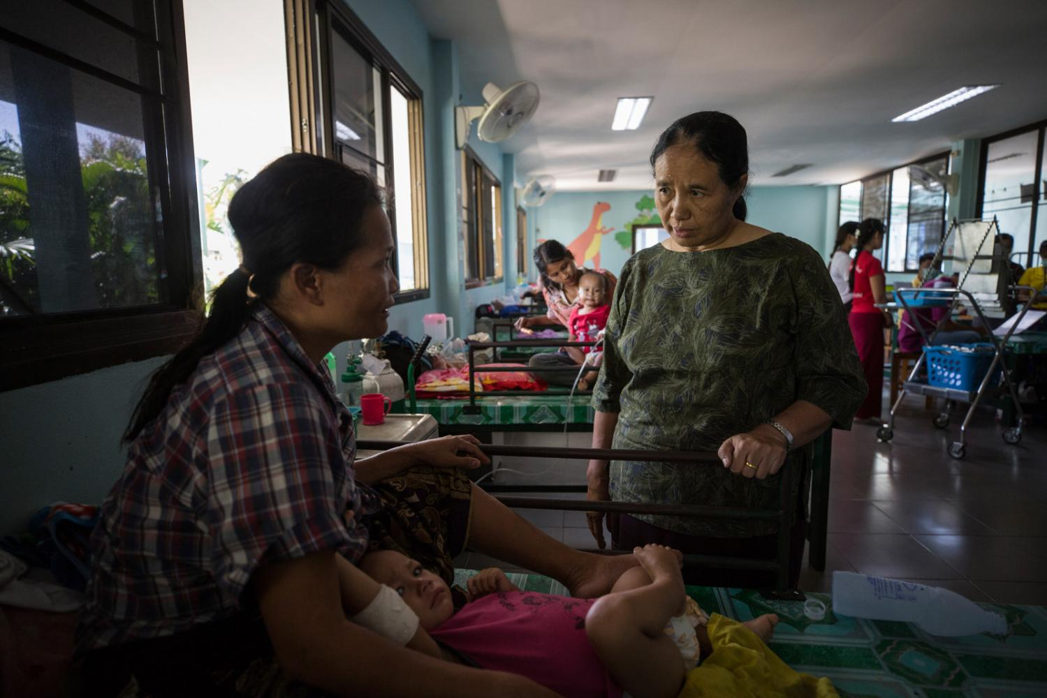Dr Cynthia Maung, founder of Mae Tao clinic, visits a patient in the inpatient ward. With dengue fever numbers high every year this year saw the outbreak of another mosquito borne disease called Chikunguniya which not only affected the patients but was also caught by over 60 of her hospital staff. Mae Sot, Thailand - October 2019