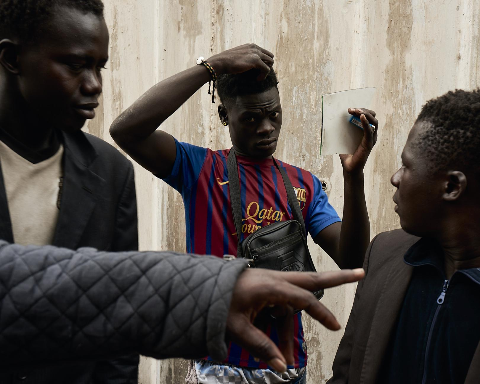 A group of young boys prepares themselves for an individual portrait session, that after went sent as a photo-postcard to their families who have lost contact since the beginning of their journey. Casablanca, Morocco, 2019.
