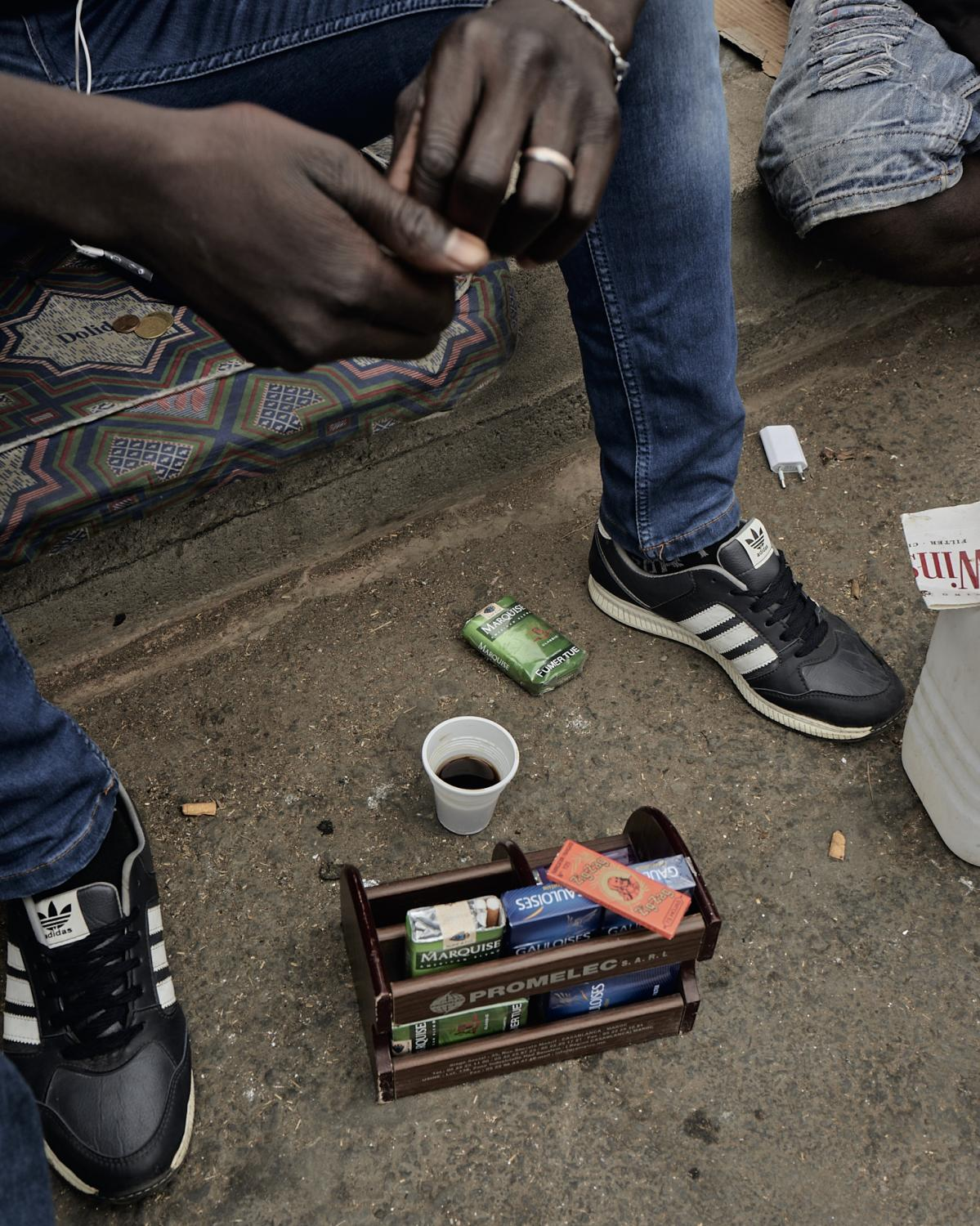 Cigarettes, coffee, and change is the daily setup for some of those kids who manage to save a little bit of money and buy things to re-sell on the light stops. Casablanca, Morocco, 2019.